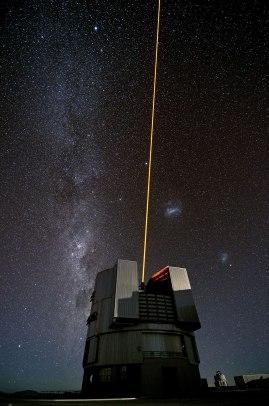 Foto di Gerhard Hüdepohl che ritrae l'ESO's Very Large Telescope (VLT) durante un test del proprio laser. Sulla sinistra, la Via Lattea. A destra, le due Nubi di Magellano